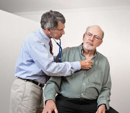 Male doctor listening to older man's heart with stethoscope