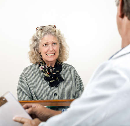 Worried frightened mature woman consults with her doctor in his office  Focus is on the woman's face
