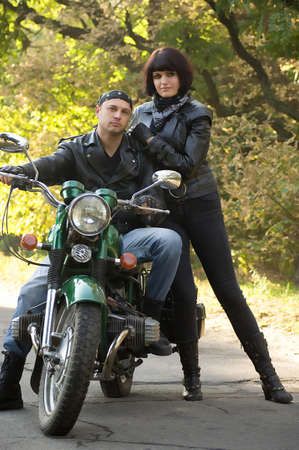 Couple of lovers sitting by motorcycle