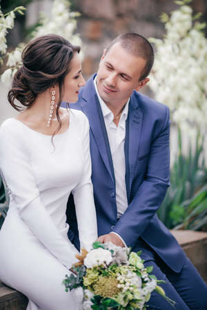 Photo pour Bride and Groom at wedding Day walking Outdoors on spring nature. Bridal couple, Happy Newlywed woman and man embracing in green park. Loving wedding couple outdoor. - image libre de droit
