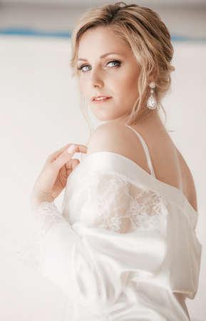 Photo pour Beautiful blonde bride with stylish make-up in white dress - image libre de droit