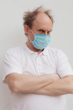 Foto de Stock Photo - Senior man in a white t-shirt wearing medical mask - Imagen libre de derechos