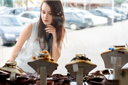 young woman with long dark hair selects a piece of jewellery in the shop window