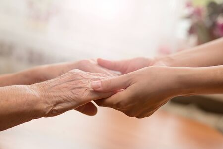 Photo for Young and old hands hold each other. The concept of love of a young and old generation of people. - Royalty Free Image