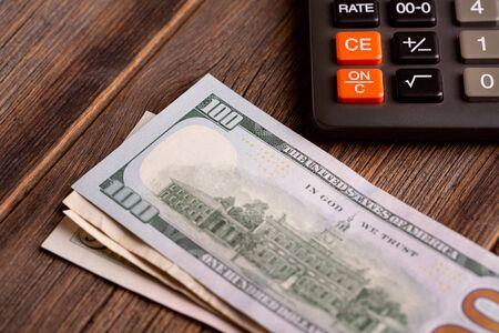 Photo pour Dollar bills and calculator on a wooden table. - image libre de droit