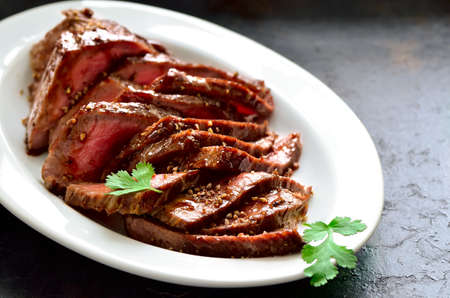 Juicy flank steak in an oval white plate decorated with cilantro leaves