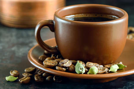 Brown cup of coffee with cardamom