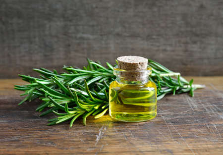 Photo for Rosemary essential oil in a glass bottle - Royalty Free Image