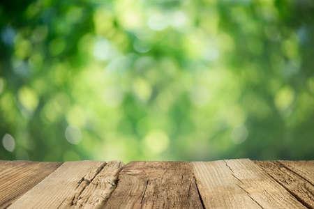 Foto de Rustic weathered table top infront of blurred garden background - Imagen libre de derechos