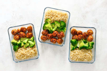 Foto de Asian style teriyaki sauce chicken meat balls with broccoli and rice prepared and put in a take away lunch boxes, view from above - Imagen libre de derechos