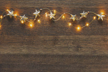 Photo pour Christmas garland with golden stars lying down on wooden background lighten up by decorative lights, view from above, space for a greeting text - image libre de droit
