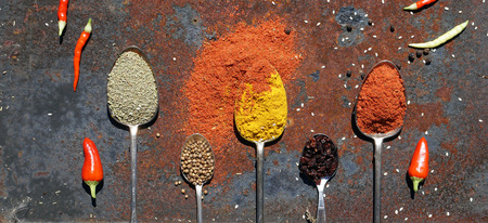 Photo for an assortment of different spices for cooking in silver spoon   . Red chilli peppers, Red Pepper Flakes, yellow turmeric, green rosemary on iron rustic background - Royalty Free Image