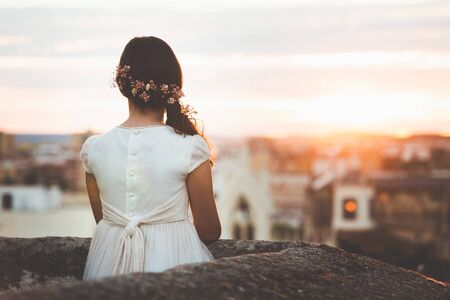 Photo pour girl in communion dress looking at city on sunset - image libre de droit