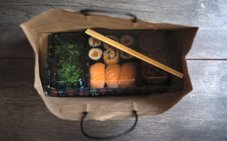 Photo for Sushi to go concept. Top view of takeaway box with sushi rolls and chopsticks in brown paper bag on wood floor. Maki. Sashimi. Salmon. Tuna. Wakame. Asian. Japanese. Paper bag.Take-away japanese food concept. - Royalty Free Image