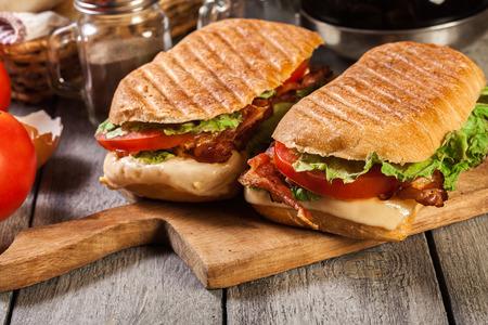 Foto de Toasted ciabatta sandwich with smoked bacon, cheese and tomato on cutting board - Imagen libre de derechos