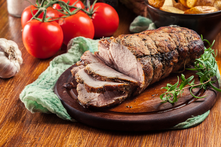 Photo pour Roasted pork loin with herbs on cutting board - image libre de droit