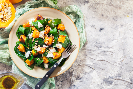 Photo pour Roasted pumpkin salad with spinach, feta and pine nuts. Autumn dish - image libre de droit