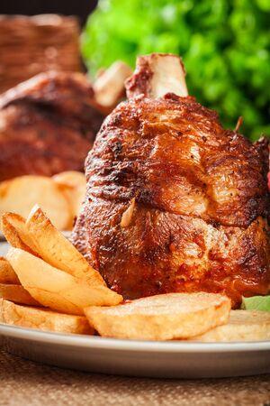 Photo pour Roasted turkey knuckle with fried potato slices on a plate. - image libre de droit