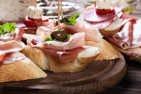Photo for Spanish tapas with slices jamon serrano, salami, olives and cheese cubes on a wooden table. Spanish cuisine - Royalty Free Image