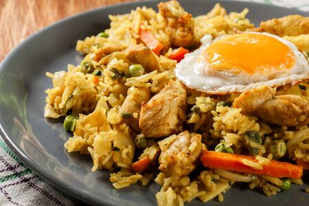 Photo pour Fried rice nasi goreng with chicken egg and vegetables on a plate. Indonesian cuisine. - image libre de droit