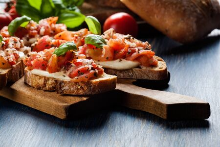 Photo for Italian bruschetta with roasted tomatoes, mozzarella cheese and herbs on a cutting board - Royalty Free Image