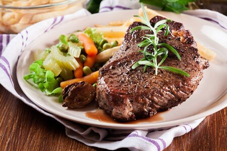 Photo pour Beef steak served with baked potatoes and vegetables - image libre de droit