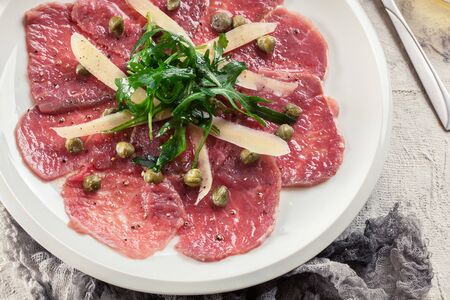Photo for Beef carpaccio with arugula and parmesan. Italian dish - Royalty Free Image