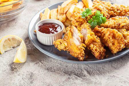 Foto für Chicken strips in cornflakes breadcrumb served with french fries - Lizenzfreies Bild