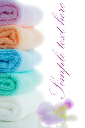 multicolor towels stacked with a orchid flower on white background and area for your text