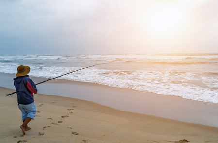Photo pour Fisherman fishing in ocean from  sand beach on sunset big game fishing trip - image libre de droit