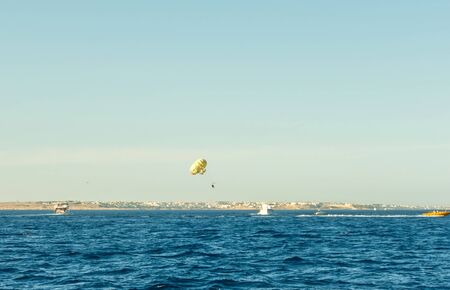 Photo pour Parasailing over red sea in blue sky with parachute Roped The Motor Boat. - image libre de droit