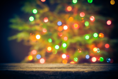 Festive background: wooden table and Christmas tree with lights