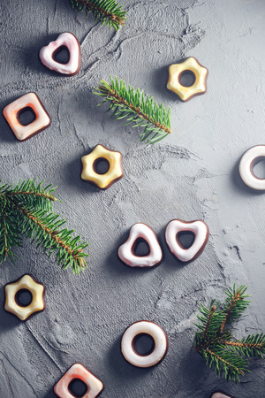 A festive background with colorful iced cookies and twig spruce