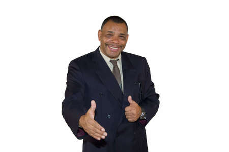 A smiling senior African-American businessman reaching out his hand for a welcoming handshake and posing with thumbs up, isolated on white backgroundの写真素材