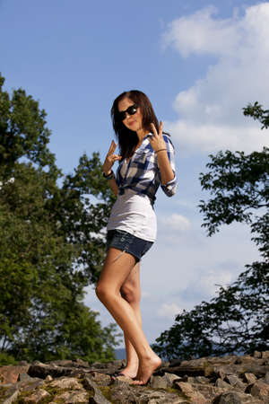 a cool and smiling brunette teenage girl with sunglasses posing in the summer sun, photographed with trees and blue sky with clouds in the background