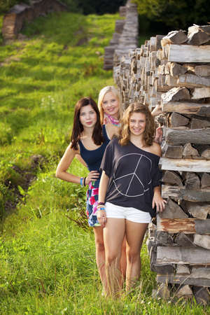 three happy and smiling teenage girls photographed standing next to a stack of wood