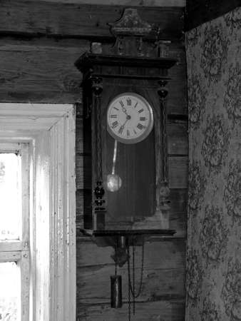 Very old clock on the wall of wooden house