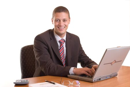 Businessman sitting smiling on his desk with laptop