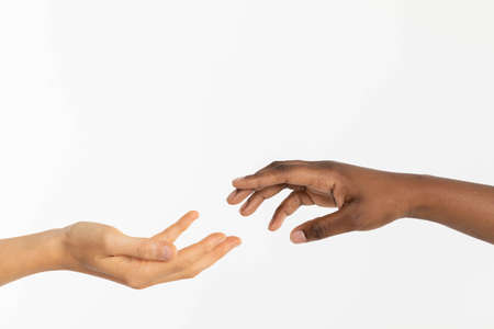 Photo pour Two gently stretched hands wishing to touch come on for a moment. The desire for love and the reconciliation of race in the world. - image libre de droit