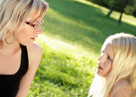 Photo pour Two young women talking seriously, summer outdoor shot - image libre de droit