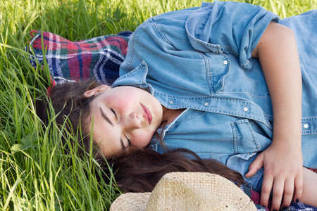 Young girl sleeping in the lawn. Summer outdoor shot.