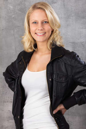 Happy smiling young blonde woman, with hands on hips looking at the camera  Studio shot against a gray background