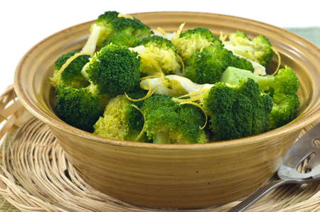 Steamed broccoli with lemon zest and Parmigiano Reggiano cheese in rustic yellow bowl