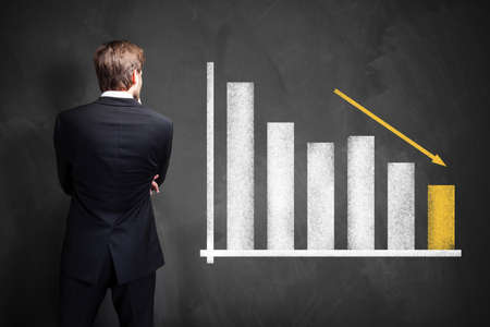 businessman in front of a declining graph