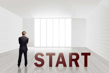 businessman standing in an empty office space besides the word \START\