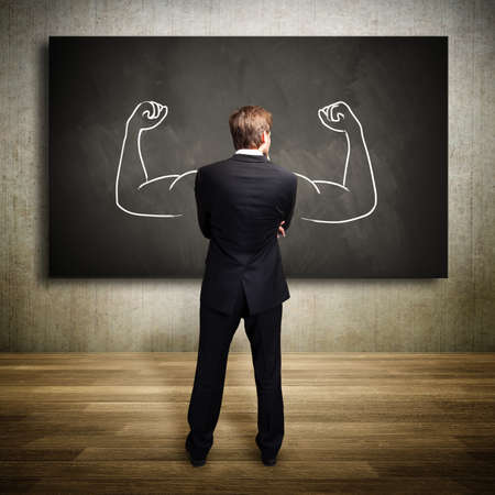 Photo for strong businessman standing in front of a chalkboard - Royalty Free Image