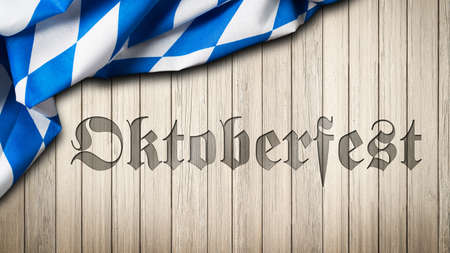 Word Oktoberfest engraved in wood with bavarian tablecloth