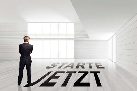 businessman in an empty white room with the slogan start now on the ground (in German)