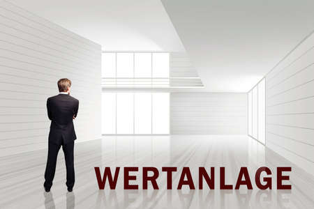 businessman in an empty white room with the word Investment in German