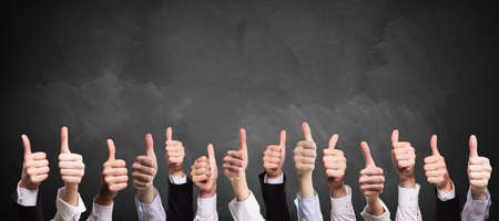 Photo pour many thumbs up in front of a blackboard - image libre de droit